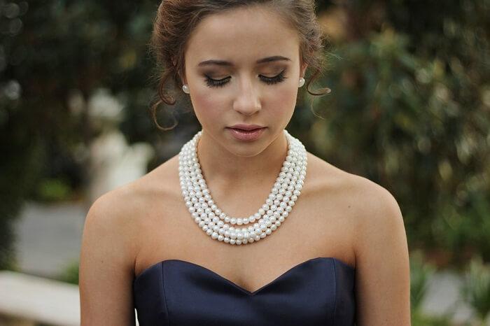 girl posing with closed eyes, makeup, elegant dress, pearl necklace, perk earrings