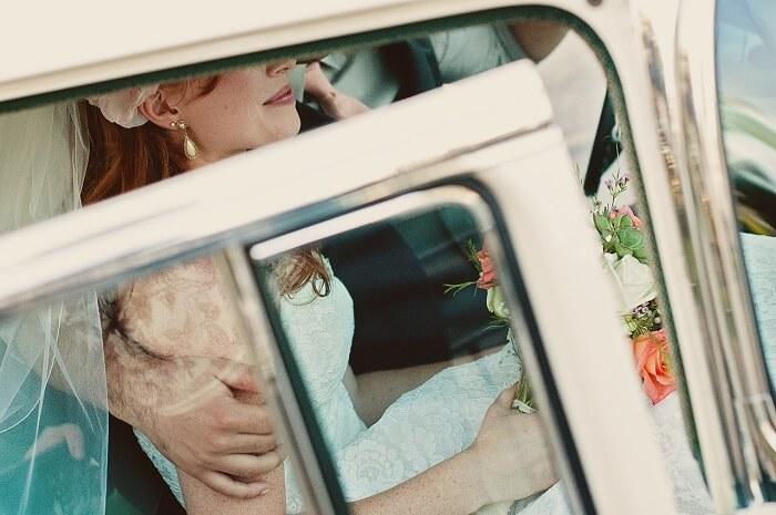 happy bride and groom in wedding car